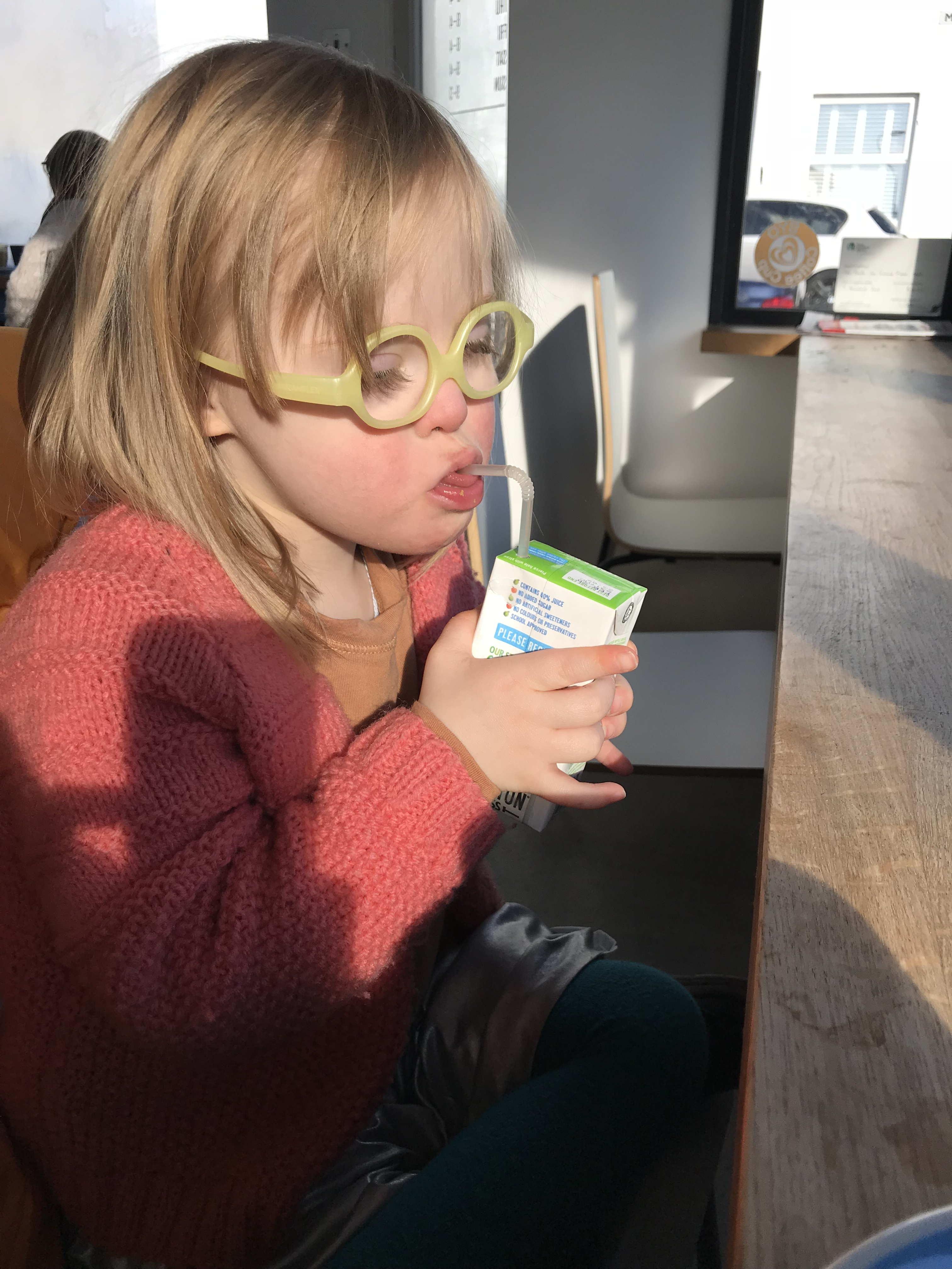 Audrey drinks her juice from a straw