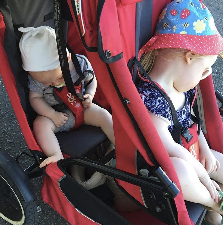 Two children sleeping in a double buggy